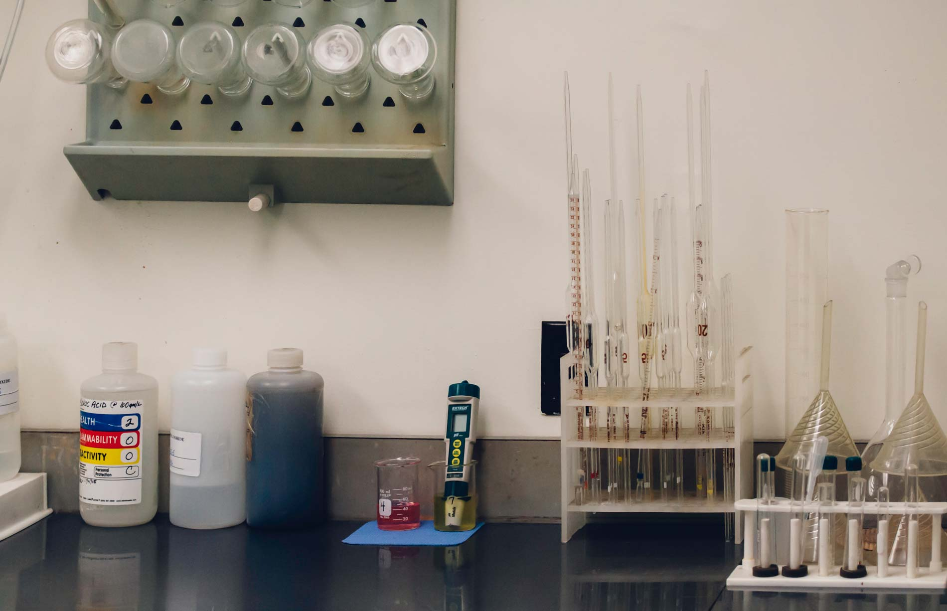 A counter with chemicals, measuring instruments, funnels, and pipettes.